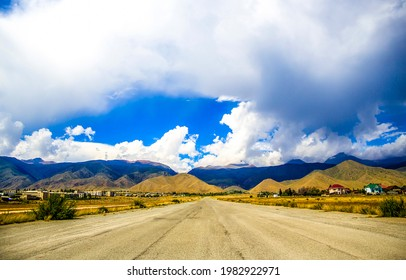 A road through a mountain valley under a cloudy sky. Mountain valley road landscape. Road in mountain valley - Shutterstock ID 1982922971