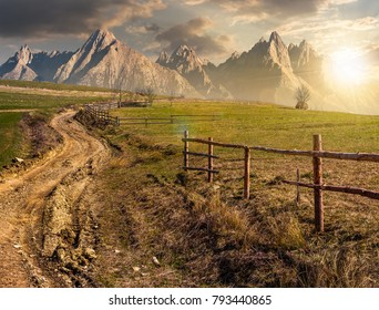 road through rural fields in mountainous area. composite imagery of agricultural countryside in springtime at sunset. wooden fence along the grassy fields on hillside