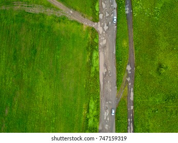 Road through rural landscape from aerial view. Green field in Siberia, Russia