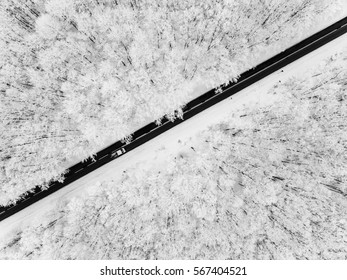 Road through snowy forest seen from a bird's eye view