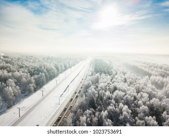 Road through taiga forest. Winter landscape from aerial view. Siberia, Russia