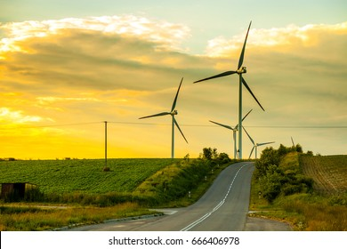 A road through the wind power at sunset.