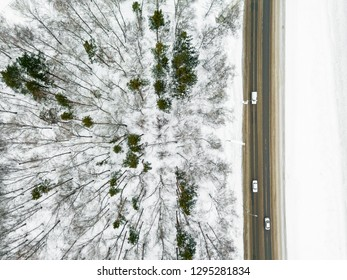 Road through the winter taiga forest from aerial view, Russia. Snowy landscape