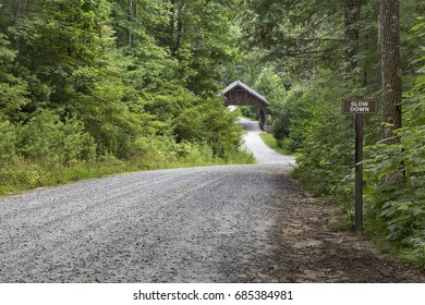road through woods to covered bridge
