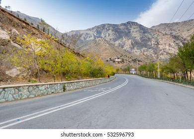 Road to the tochal mountain with rocks and trees in autumn against blue sky, Tehran, Iran. Tochal is a popular recreational region for Tehran's residents