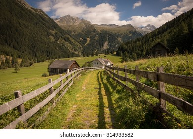 Road towards Farmhouses with Fences and Mountains in the Background in Summer, Mallnitz, High Tauern, Alps, Austria, Europe