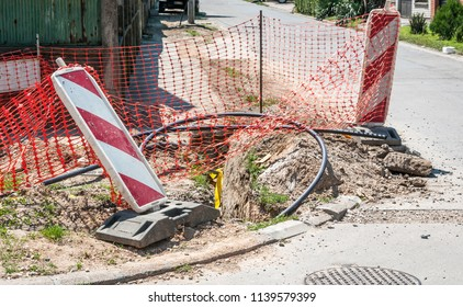 Road traffic sign work ahead with red and white barriers on the street construction site in the city and orange safety net for internet or telephone underground cables