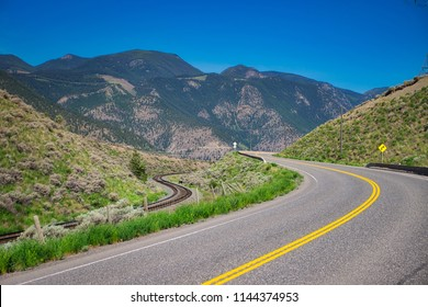 Road and train track side by side in the mountains. Transportation by car or train parallel next to each other.