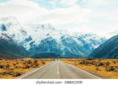 Road travel in the green mountains of New Zealand view from car window. Scenic peaks and ridges. Beautiful background of amazing nature.