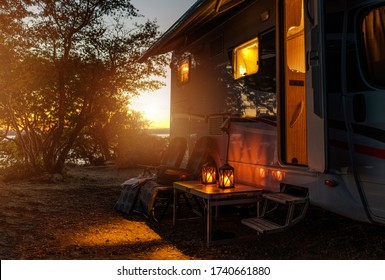 Road Trip Adventures. Calm Warm Night on a Camping. Camper Van, Outdoor Chairs and Romantic Light From Lanterns. Vacation in Recreational Vehicle.