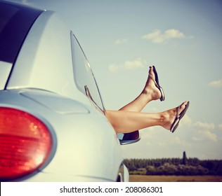 Road trip concept. Woman Hangs Her legs out of window in car.