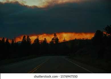 Road Trip during wildfires on the horizon in Arizona. A wildfire burns through the Coconino National Forest, north of Flagstaff. Climate change, wildfires, dramatic views.