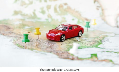 Road trip at homeland - red car goes on map across territory of USA. Route of automobile travel is laid on by office buttons. Domestic tourism.