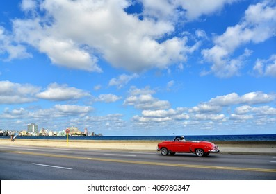 Road trip on a summers day in Havana. Travel with car on seafront, red oldtimer.
