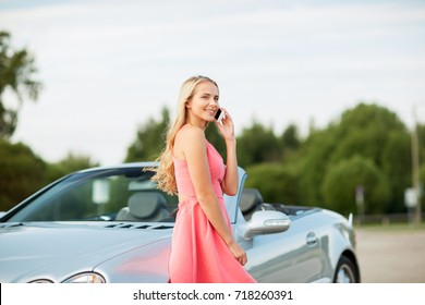 road trip, technology and communication concept - happy young woman calling on smartphone at convertible car