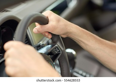 road trip, transport and people concept - close up of male hands driving car and holding wheel