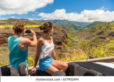 Road trip vacation car couple taking pictures of Hawaii nature landscape with smartphone camera app. Young people relaxing in convertible car on summer holidays. Travel lifestyle.