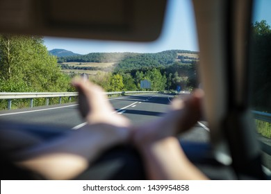 Road trip. View at a road from the car. Adventure and leisure. Feet are on the car dashboard. Green hills and mountains are on the background. Traveling in Spain, Catalan vacation.