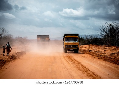 Road to Tsavo East National Park gate, Kenya - August 2018: Group of African black men working for the construction of a road over an orange sandy off-road path. tractors, bulldozers, heavy trucks