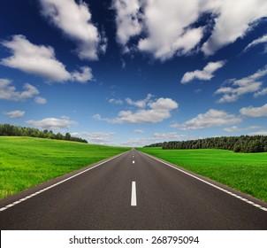 Road under beautiful sky between green hills