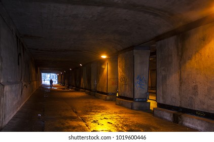 Road under a bridge with artificial lighting