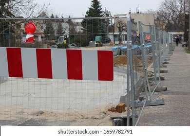Road under construction, fenced with a warning sign.