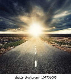 the road under dramatic sunset with sun rays