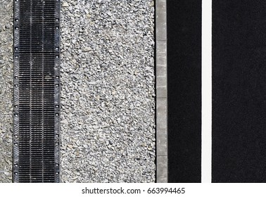 Road view from above, black asphalt, white dividing strip, concrete curb, rainwater drainage system, runoff, rubble. Highway background, roadside top view