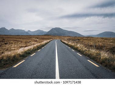 Road view of mountains, hills and fields, taken along the Wild Atlantic Way in Western Ireland in summer