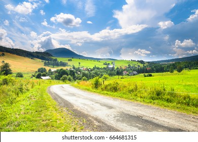 Road, village and mountain summer landscape