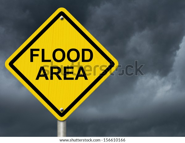 A road warning sign against a stormy sky with words Flood Area, Flood Warning