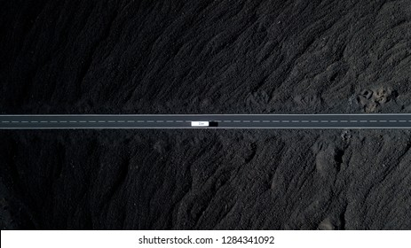 The road with white lines is surrounded by black volcanic lava. Sticking rocks. Dangerous adventure of incredible beauty. Top view, drone footage. Minimalistic landscape. White car in motion.