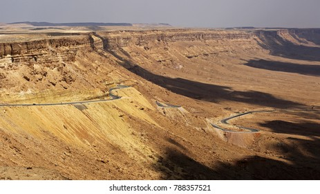 Road winding down to the bottom of Mitzpe Ramon crater in Negev desert, Israel. Mitzpe Ramon crater is the world's largest erosion crater created 220 million years ago when oceans covered the area.