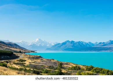 A road winds along the edge of a turquoise blue lake with mountains in the distance