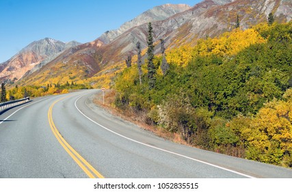 The road winds around the mountain base revealing a photo opportunity sign scenic wild area of Alaska