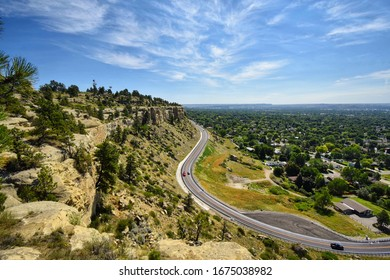 A road winds through Billings Montana. Very few people on the roads driving. Desert like.