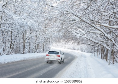 Road in winter forest. White car goes across woods after snowfall. Scenic view of tunnel with snowy trees. Nice scenery of frozen way covered snow.