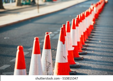 Road work. Orange traffic cones in the middle of the street.