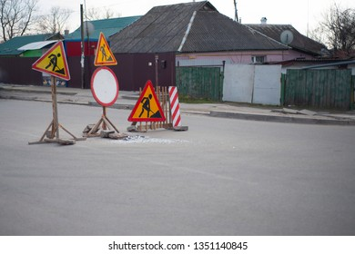 Road work in the village. Many signs - roadworks, stop, no pass.
