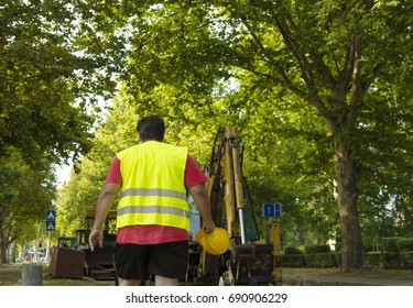 Road Worker back.Walk with yellow helmet  in hand, against a road machinery.