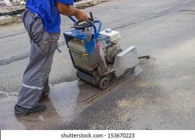 Road worker cutting asphalt road, working on the road reconstruction. saw cutting asphalt with water spraying to hold down dust.