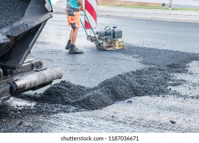 Road workers compact the asphalt with a vibrating rammer on the road, Germany