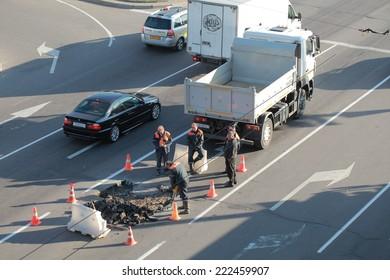 road workers jackhammer breaking asphalt roadway.Belarus, Minsk,Oktober,4,2014