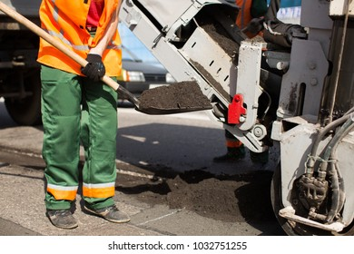 Road workers repair work. work sleeps shovel the material into the machine.