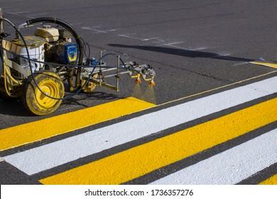 Straßenarbeiter benutzen Heißklebemaschinen, um Fußgängerübergänge auf Asphaltstraßfläche in der Stadt zu malen.