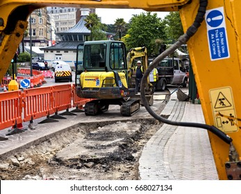 Road works, Bournemouth, Dorset, June 2017; workmen re-lay pavement and road in city centre; editorial