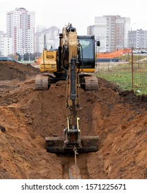 road works in the city. excavator digs a pit for sewer work.