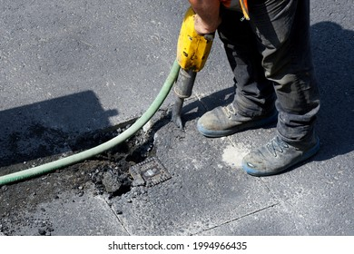 road works on a gas pipeline, prising up the asphalt of a road with a jackhammer to expose a gas connection - Shutterstock ID 1994966435