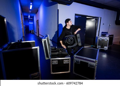 Roadie lifting a big moving head light out of a flightcase