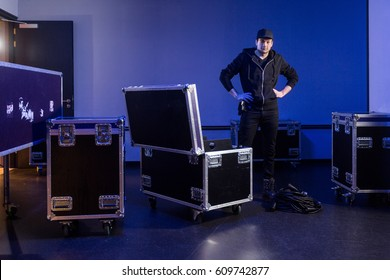 Roadie standing next to a flightcase with cables that he just unpacked